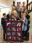 Photo of women holding a patchwork quilt