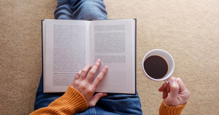 image of someone reading a book with a coffee